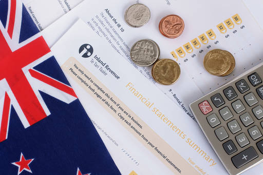 New Zealand flag, coins, and tax forms