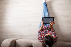 woman sitting on floor using tablet