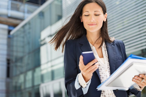 Woman holding papers and looking at mobile phone