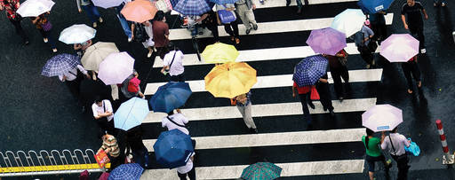 Insurance | Crowd crossing a street carrying open umbrellas