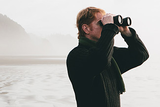 Man looking through binoculars with island in background
