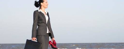Business woman walking on beach