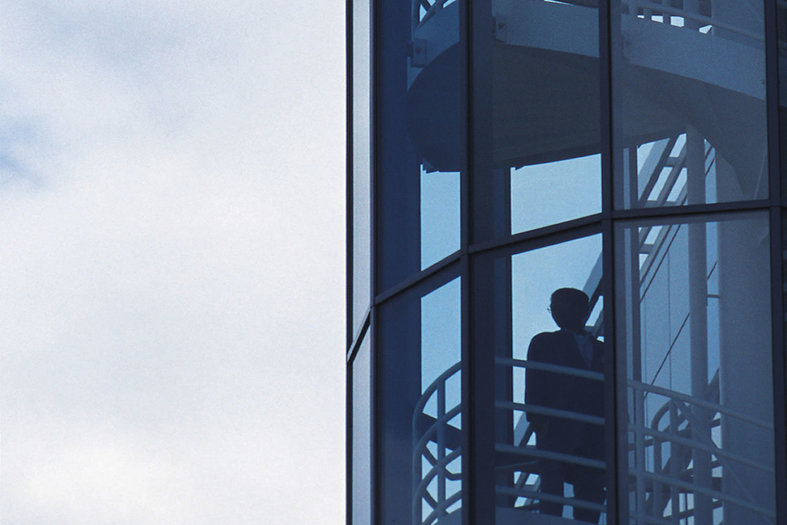silhouette in staircase staring through glass in modern building