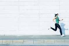 Woman jogging with white wall in background