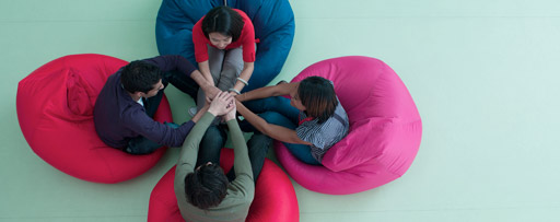 Four people sitting in coloured bean bags holding hands