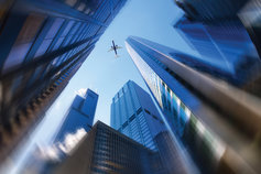 aeroplane flying between two buildings