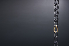 Chain with gold link against a black wall