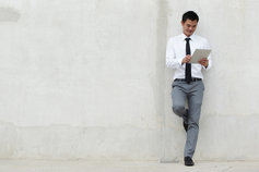 Newsletter registration - man leaning on wall holding tablet