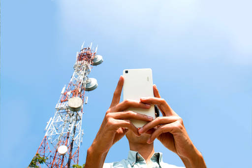 Smart phone user next to a telecommunication tower