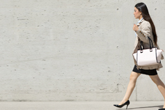 Woman carrying handbag walking in front of concrete wall