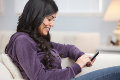 Woman using phone sitting on couch