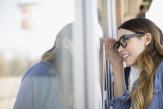 Woman wearing glasses looking in window