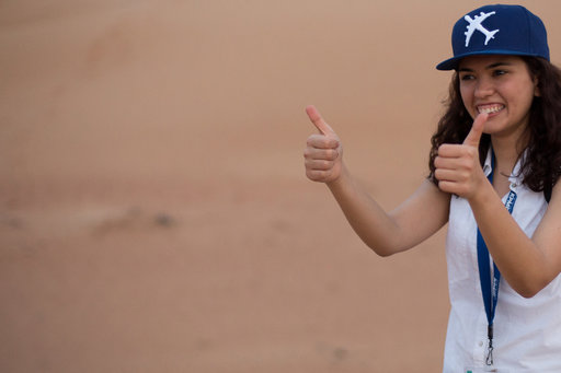 woman wearing a baseball cap giving two thumbs up