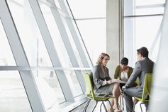 business people meeting by glass wall