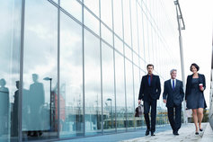 business people walking by glass building