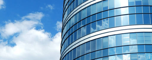 Curved modern glass office building with blue sky reflected