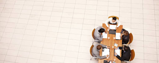 Insurance CEO Survey: Our views - photo people sitting down on a long brown desk from above