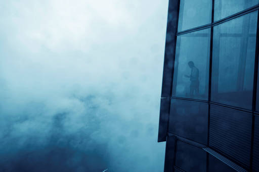 Man in office skyscraper overlooking the fog