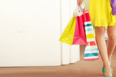 Revenue | Woman in a yellow dress carrying colourful shopping bags ,