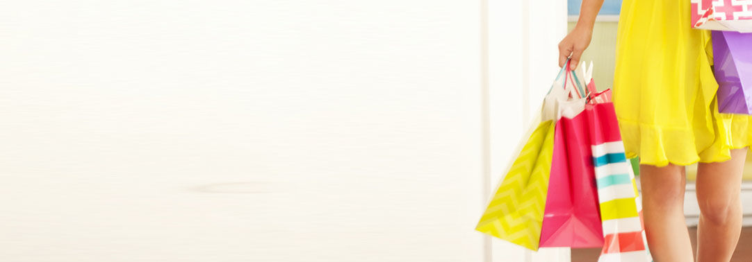 KPMG IFRS revenue topic image: Woman in a yellow dress carrying colourful shopping bags