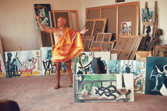 artist posing with paintings