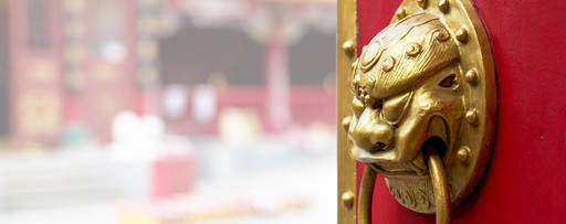 Red door with Asian handle ajar