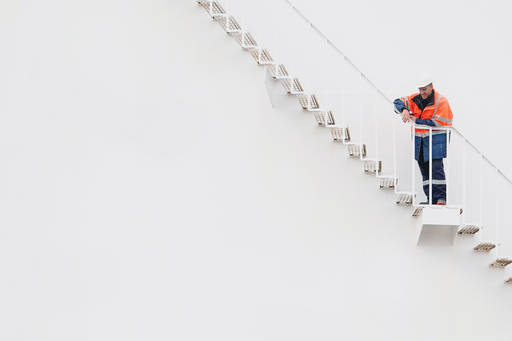 man looking down from stairs on a white wall