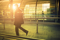 Man walking through platform in sunlight