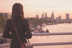 Woman on a bridge over the Thames looking out at the City of London