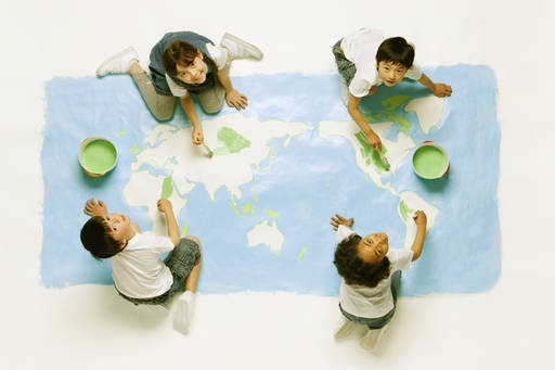 topview of kids painting a mural of the world map