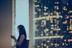 Woman checking mobile with blur lighted building in background