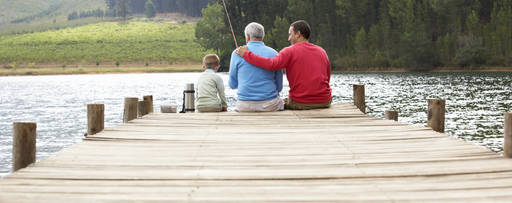 Three generations sitting on a pier