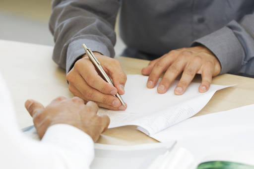 close-up of man signing papers