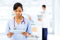 Doctor wearing stethoscope holding tablet with blur background