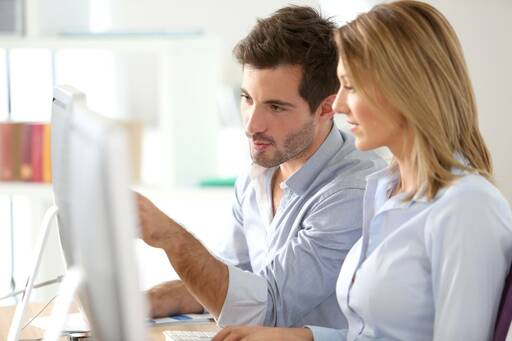 Man and woman working on desktop computer