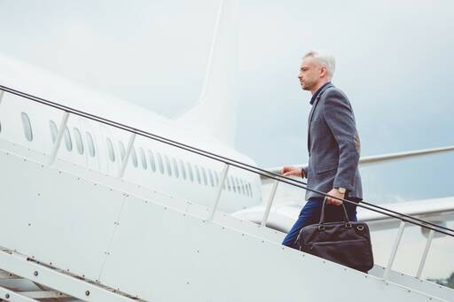 Man with suitcase boarding plane