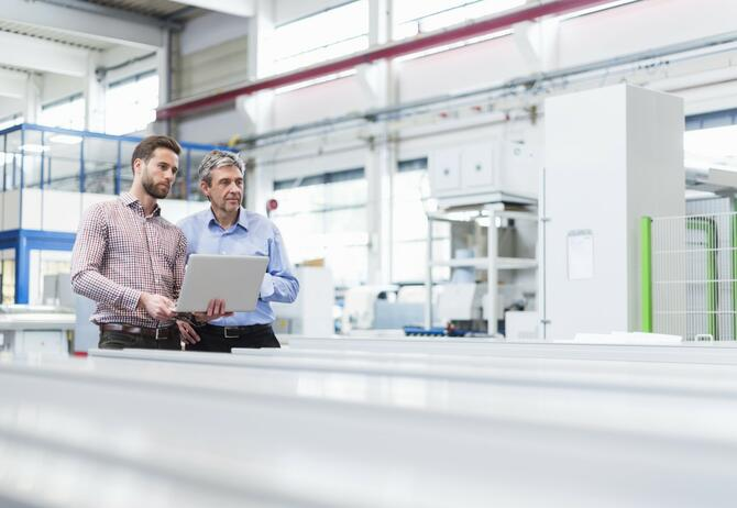 Two men standing in factory discussing