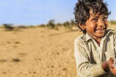 Boy in the desert happy to have water poured into his hands