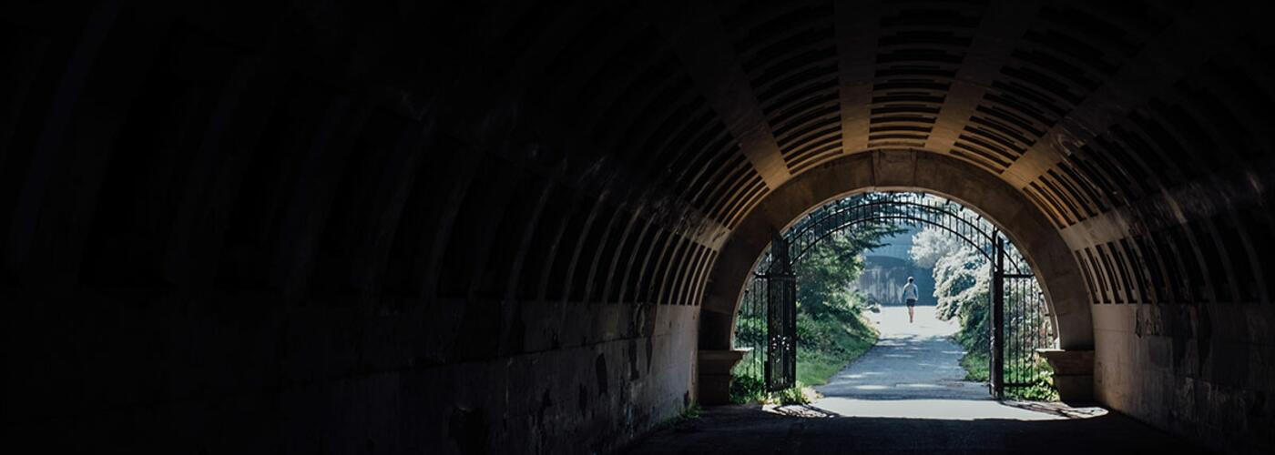 man-waling-out-of-tunnel