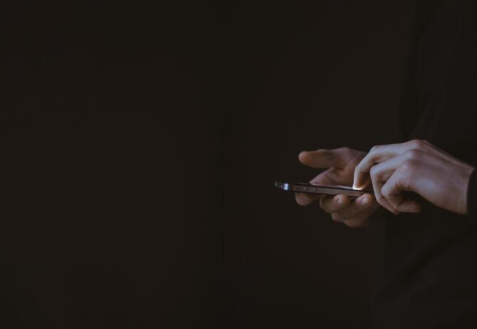 digital, hand holding a mobile phone on dark background