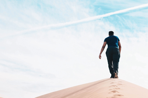 man walking up a sand hill