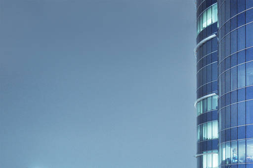 Directors' remuneration in FTSE SmallCap companies - glass building with blue sky