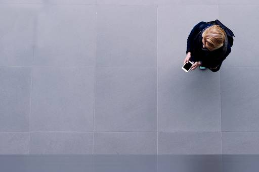 The value of fintech - photo of a woman looking at her phone, taken from above looking down.
