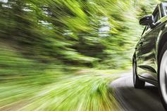 2018 Global Automotive Executive Survey - car driving with blurry green countryside background