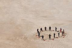 People standing in a circle in the sand