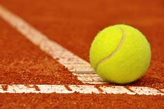 Image of tennis ball on red sand