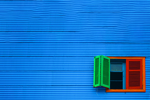 Reocos and real state - multicolored-window-against-blue-brick-wall-1500
