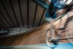 Person cycling in stadium blurred