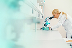 Woman using microscope in lab - Life sciences