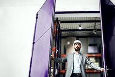 UK Economic outlook- man-opening-a-purple-door-wearing-construction